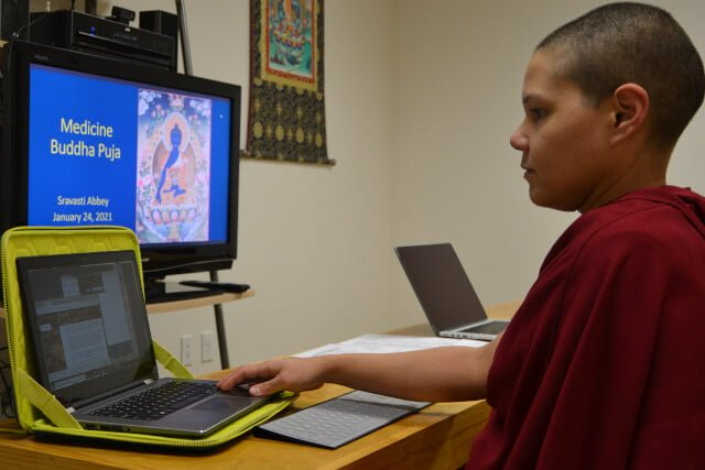 "Nun faces computer screen that says ""Medicine Buddha Puja"""