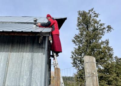 Monk on ladder next to metal building
