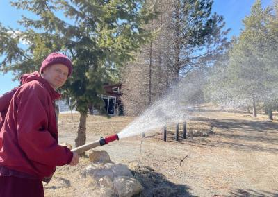 Monk sprays water from fire hose