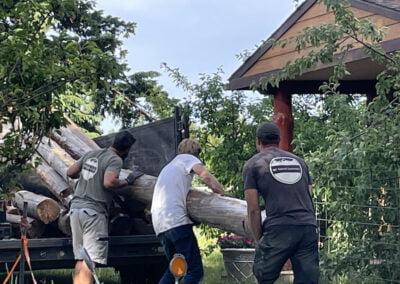 Men put log in truck.