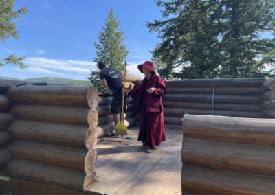 Abbess sweeps cabin.