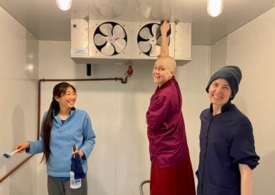 Nun, trainee, and guest clean refrigerator.