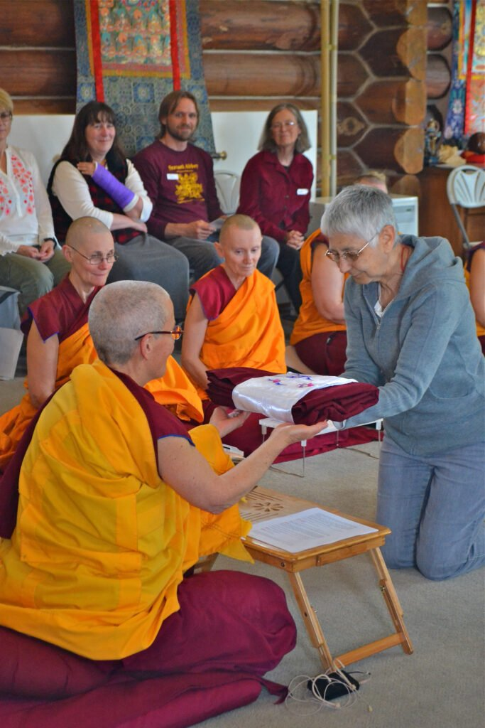 The sangha receives the robe of merit.