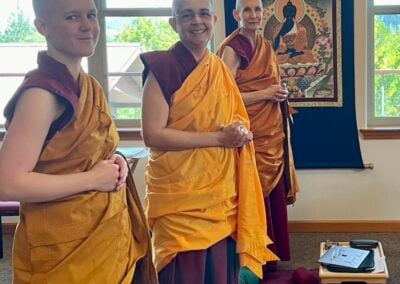 Nuns in front of Medicine Buddha painting.