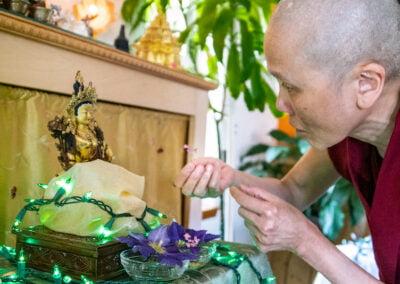 Nun places flower on altar.