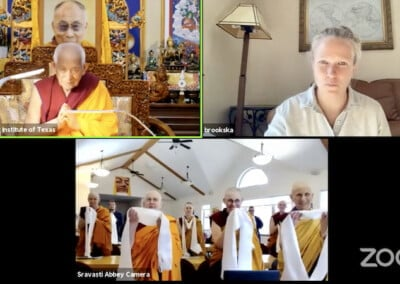 Zoom screen showing Tibetan monk, translator, and monastic community with scarves